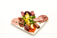 Plate of cold cuts and cheese with raw vegetables