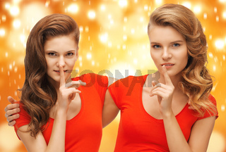 two teenage girls showing hush gesture