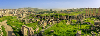 Panorama overview of the Roman site of Gerasa, Jerash, Jordan, with ruins, pillars and remains of the old city clearly visible. Green grass and blue sky on a sunny day in spring.