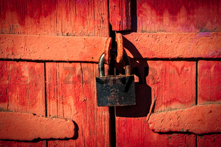 Closed lock on gates made of wooden planks and painted in red, retro