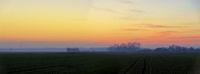 Landschaft mit Feldern und orangem Himmel