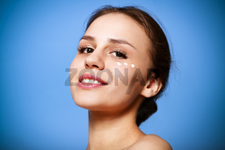Young woman with cream dots on face