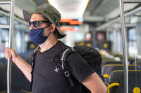 Man with a mask talking traveling in the train during Covid19 pandemic
