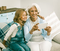Grandma And Her Cheerful Granddaughter Making Selfie Photos