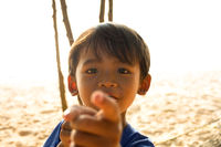 A young local boy from Cambodia, playfully looking and pointing at the camera.