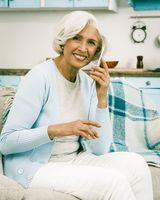 Italian white haired smiling woman making a phone call