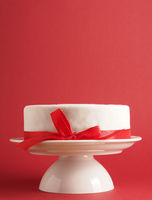 A white wedding or birthday cake with a red bow on a white cake stand