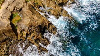 Wild Ocean water from above - Waves hitting the rocks
