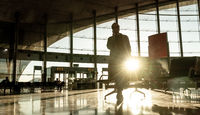 Silhouette of woman stucked at airport terminal over flight cancellation,calling family, sitting in almost empty airport terminal due to coronavirus pandemic, Covid 19, outbreak travel restrictions