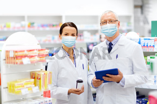 apothecaries in masks with tablet pc at pharmacy