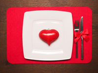 White plate with a red heart shape on wooden table