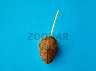 coconut drink with paper straw on blue background
