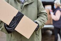 Paketbote bei Lieferung von Paket zu Weihnachten