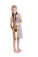 young girl in dress playing saxophone standing