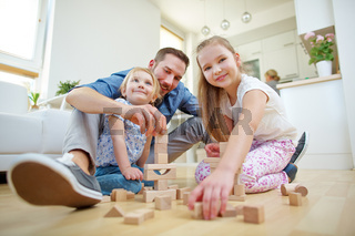 Vater und Kinder spielen mit Bausteinen