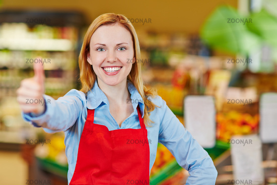 Verkäuferin im Supermarkt hält Daumen hoch