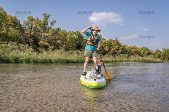paddling stand up paddleboard with a pitbull dog