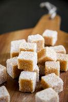 Brown cane sugar cubes on a cutting board