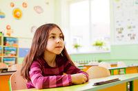 Schoolgirl sitting at her desk in empty classroom