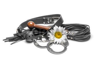 bdsm black leather gag with handcuffs and a yellow daisy flower on a white background