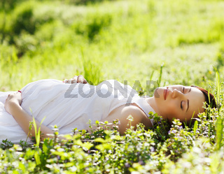 Beautiful pregnant woman on grass in the spring park