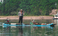Man on the bamboo boat crossing Li River in Yangshuo