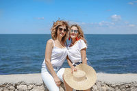 Adult mother and daughter hugging near sea