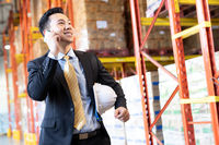 Portrait asian businessman making a call in distribution warehouse