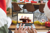 Rear view of man and son in santa hats waving while having a videocall with couple in santa hats wav