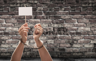Handcuffed Female Hand Holding Blank Sign Against Aged Brick Wall