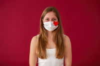 Woman wearing white cloth face mask and looking into camera from front view on red background.