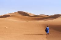 Eine Person laeuft durch Sandduenen in der Sahara