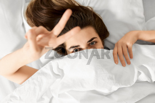 young woman lying in bed and showing peace