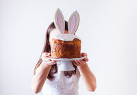 Girl holding Easter cake with bunny ears