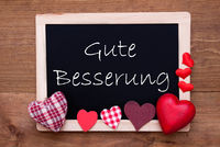 Balckboard With Red Heart Decoration, Text Gute Besserung Means Get Well Soon