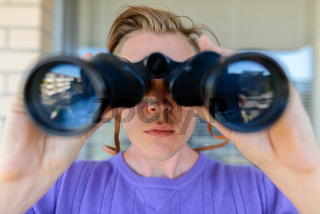 Face of young handsome man looking through binoculars