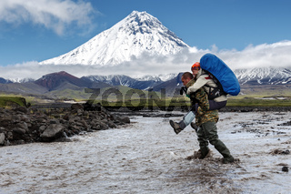 Strong tourist carries woman on her back to cross muddy mountain river