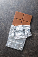 Wrapped chocolate bar in aluminum foil.