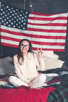 Pretty female in casualwear on bed with American flag on the wall
