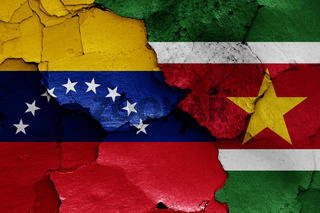 flags of Venezuela and Suriname painted on cracked wall