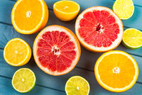 juicy oranges, grapefruits, limes and lemons lie on a blue wooden table. view from above