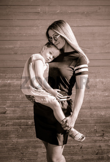 Beautiful mother holding her adorable three year old daughter