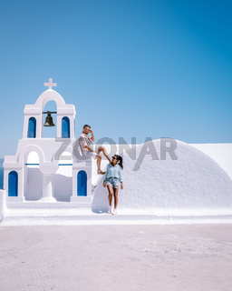 Santorini Greece, young couple on luxury vacation at the Island of Santorini watching sunrise by the blue dome church and whitewashed village of Oia Santorini Greece during sunrise, men and woman on holiday in Greece
