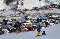Two snowboarders on snowy ski slope in high winter mountains and sunlit village