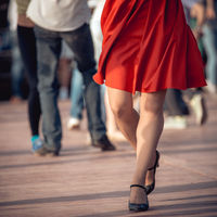 people are dancing outdoors in the park at sunny day. beautiful female feet in dancing shoes in the foreground and red skirt