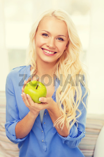 smiling woman with green apple at home