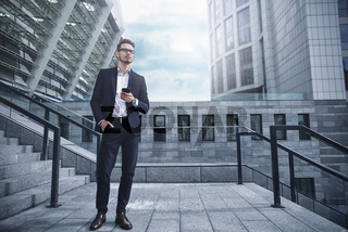 Business man stand at street holding a smartphone in office park