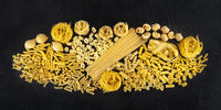 Italian pasta panorama, a flat lay of a variety of pasta kinds, overhead shot on a black background