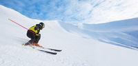 Alpine skier skiing in mountains
