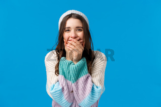Emotions, new year, winter holidays concept. Cheerful charismatic feminine young woman laughing out loud, chuckle and shut mouth with hands, giggle over something funny, blue background